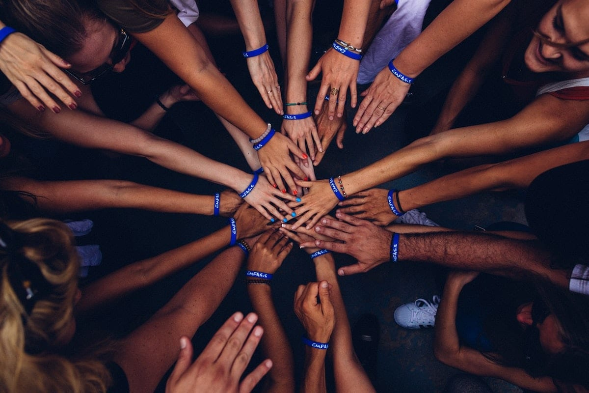 Group of people putting their hands in