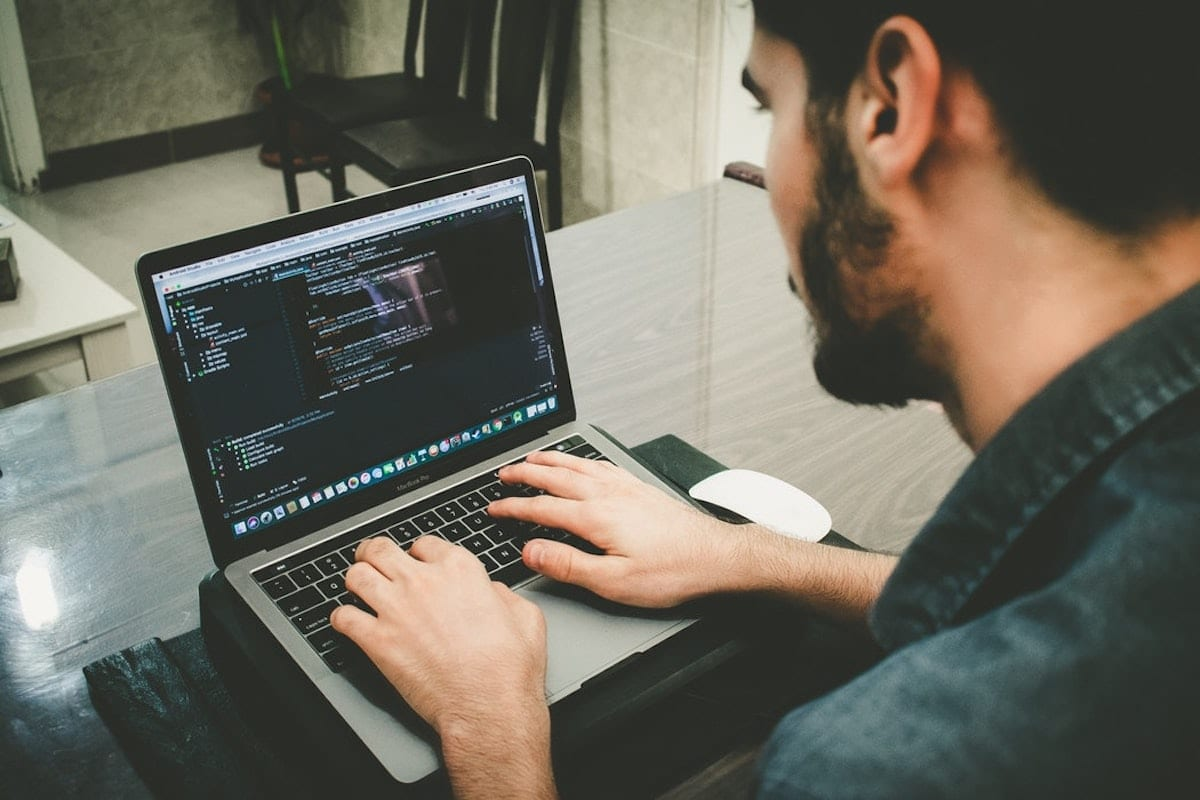 image of a software engineer coding on a laptop.
