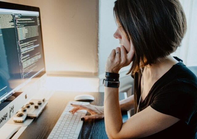 Woman wearing black shirt sitting at desk, working on computer