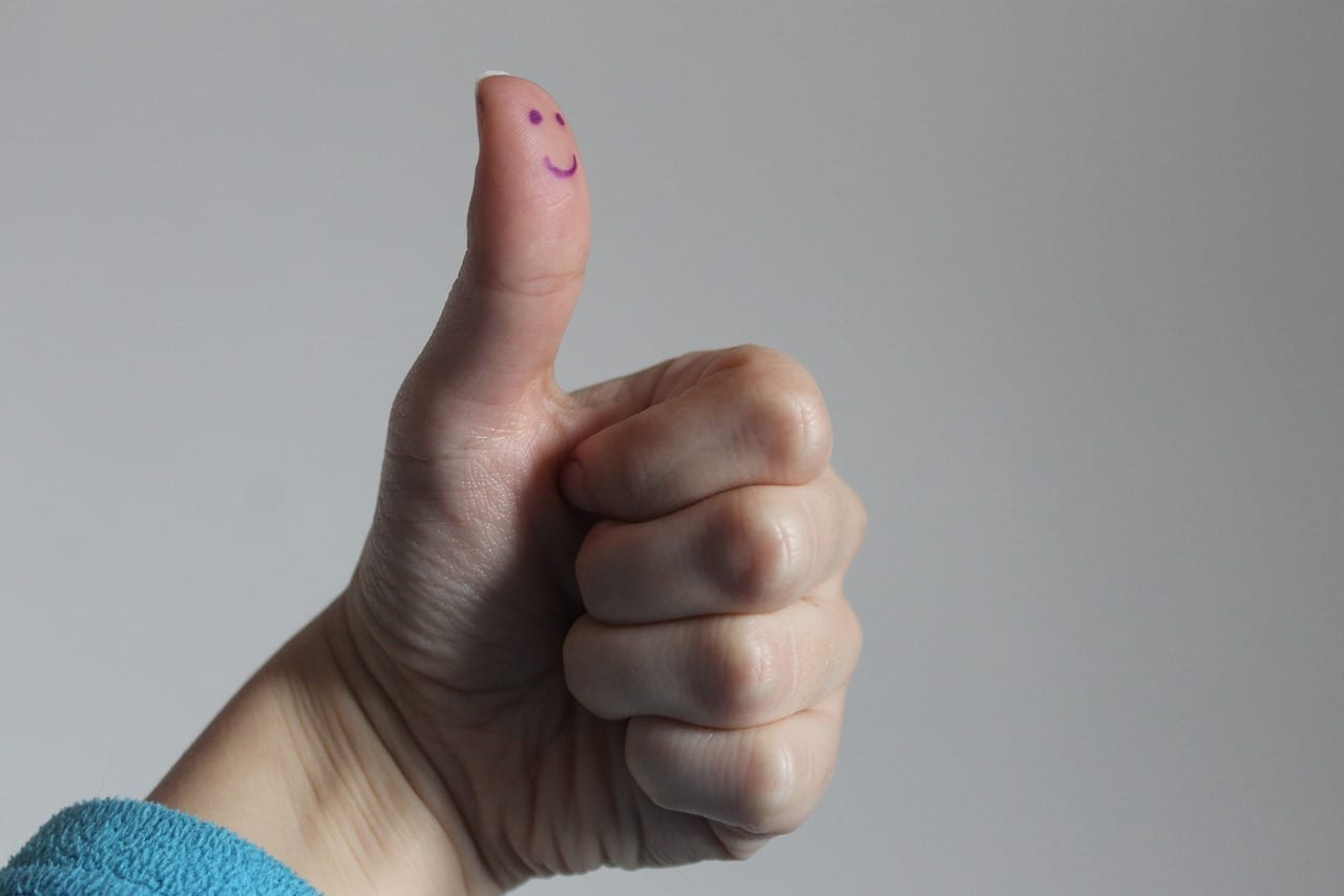 Hand giving thumbs up with smiley face.