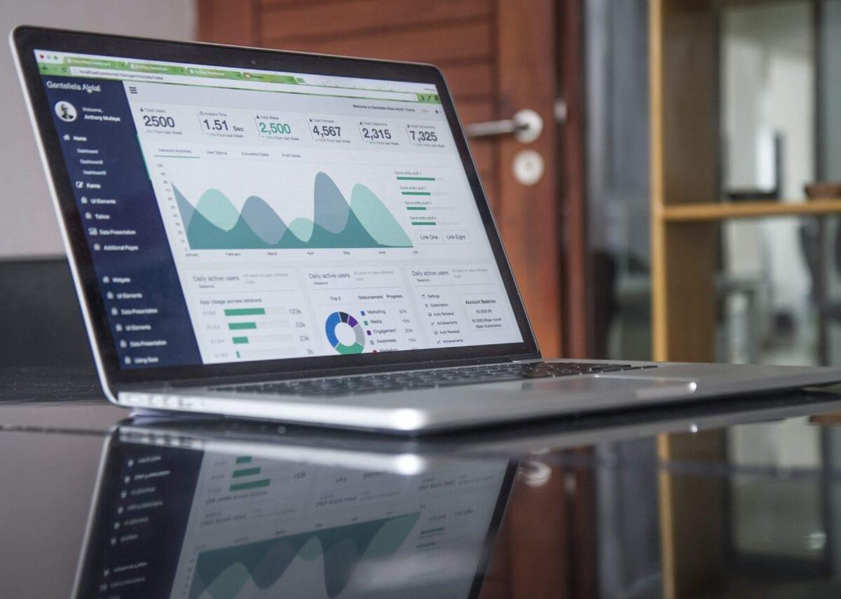 Open laptop on desk displaying graphs of data