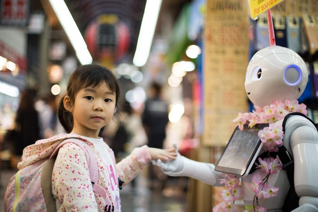 A child shaking hands with a robot.