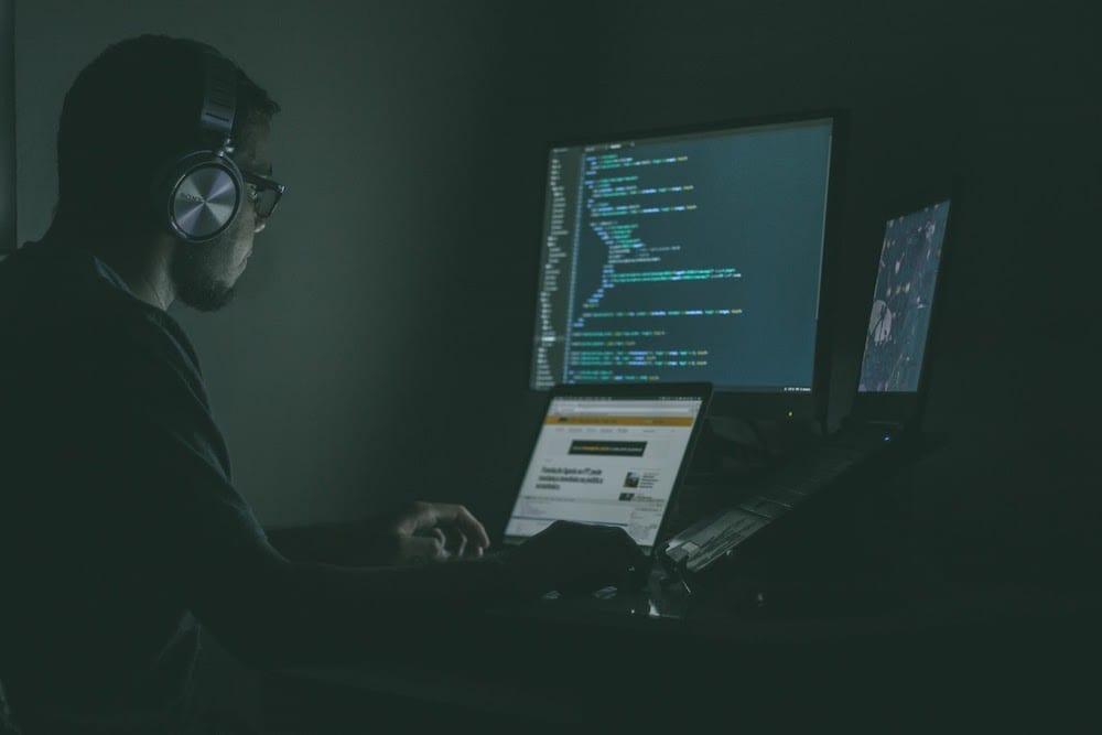 Man wearing headphones looking at multiple computer screens