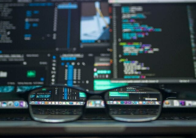A pair of glasses sit on a table facing a computer screen.