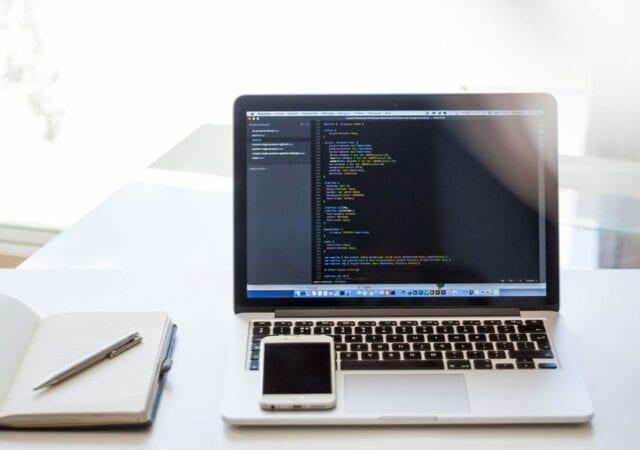 A laptop displaying HTML