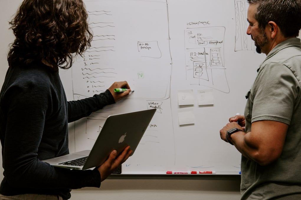 People at whiteboard analyzing data