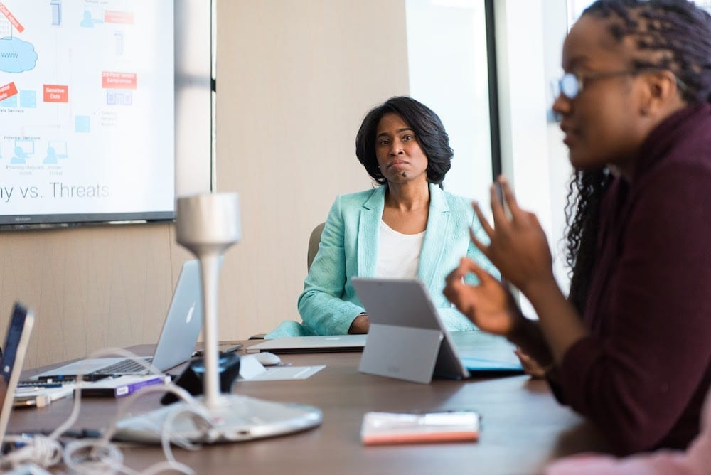 Woman in teal blazer sitting at end of meeting table listening to another woman speak