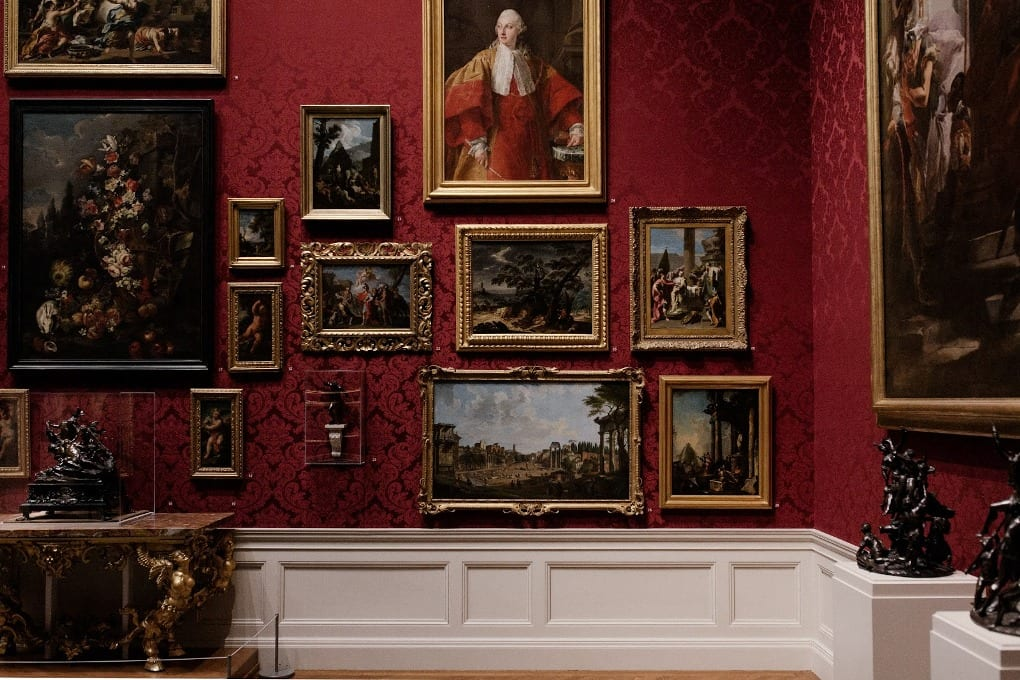 A museum with a variety of portraits on the wall.