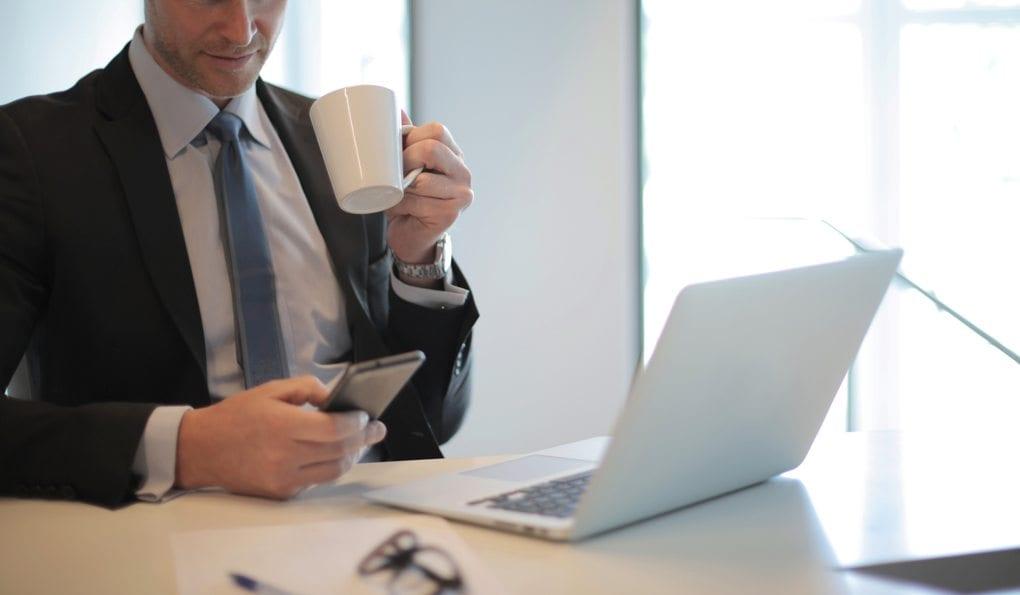 man in black suit drinking coffee