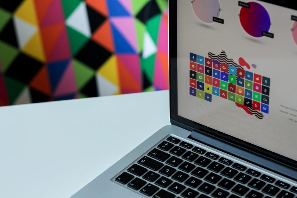A silver laptop with geometric colorful patterns and logos