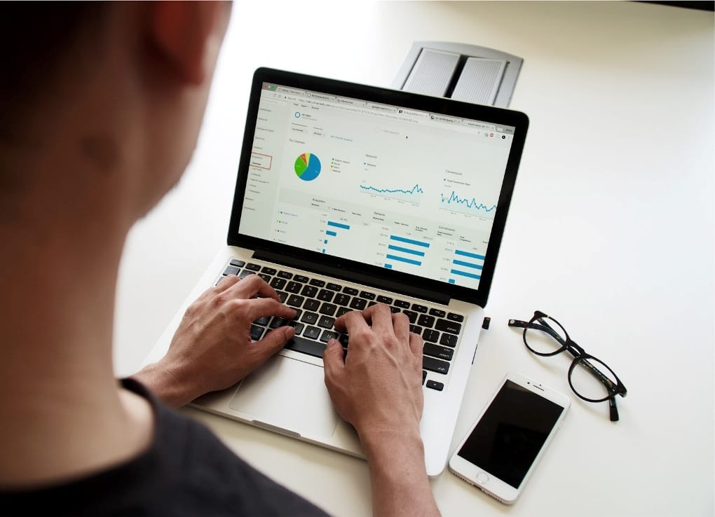 Man creating colorful graphs and charts on laptop