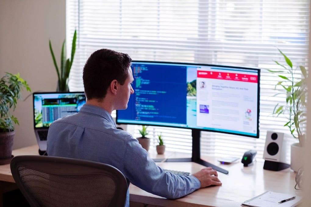 Man in blue dress shirt sitting in front of desktop monitor screen displaying code