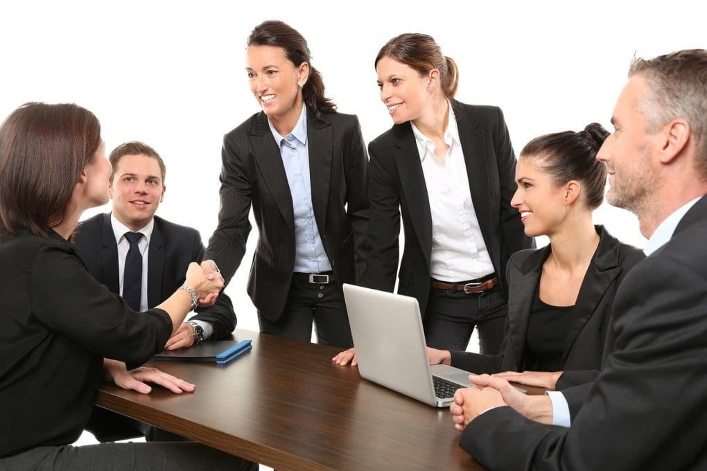 Six smiling people surround a conference table with a laptop and folder on it, two of whom are shaking hands