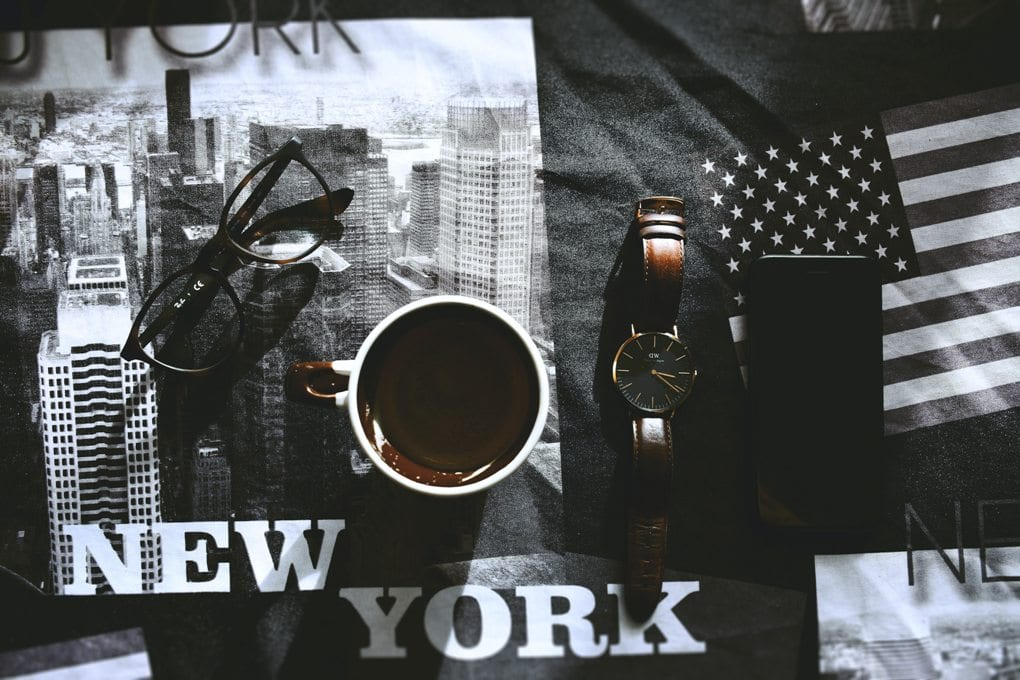 black and white new york images a cup of coffee glasses and a brown watch