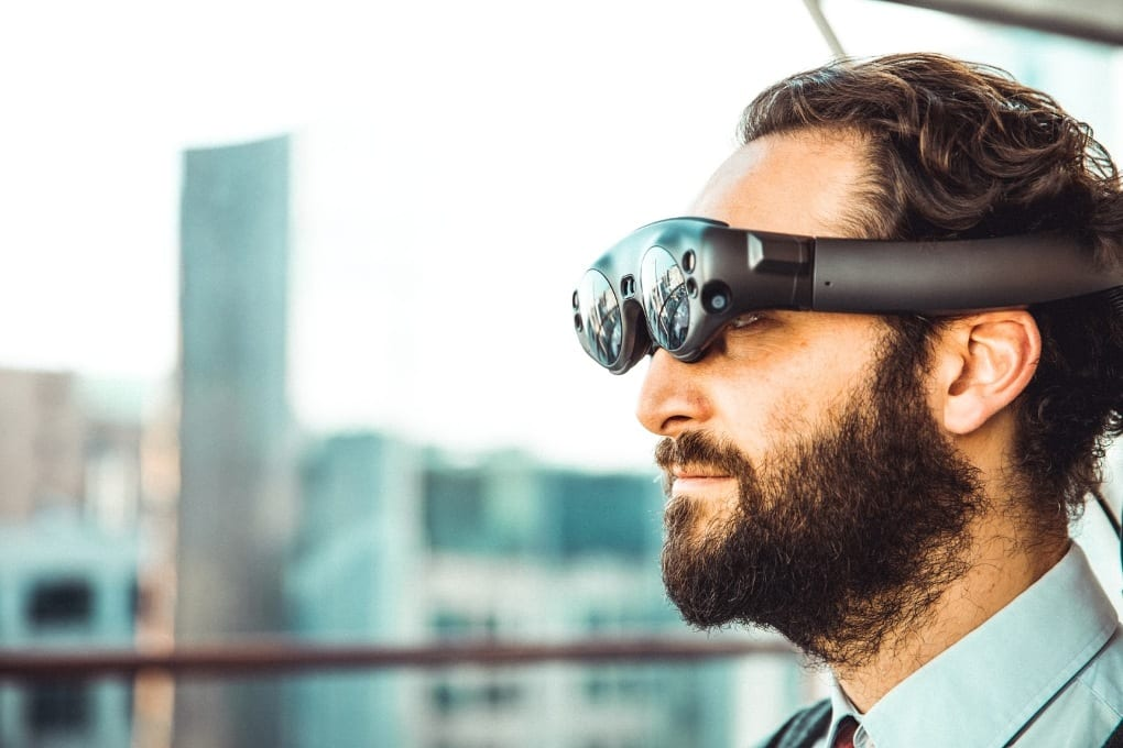 Against a blurry cityscape background, a bearded man wearing a collared shirt, pictured from the shoulders up, looks through a pair of VR goggles.