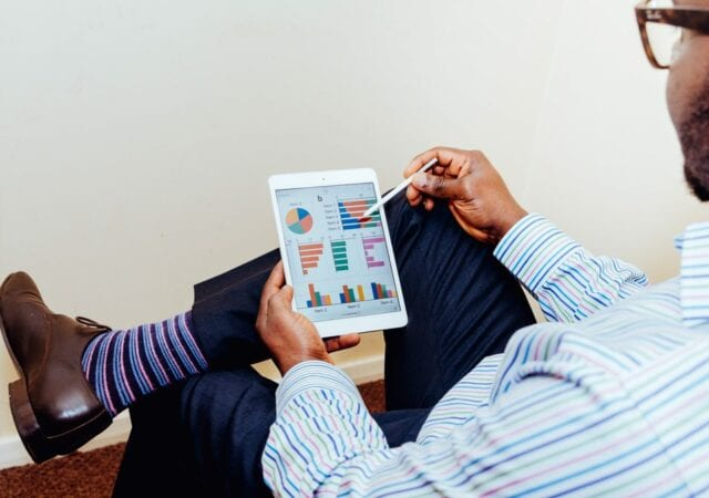 Man in striped button-up shirt holding white tablet displaying various colorful graphs and charts