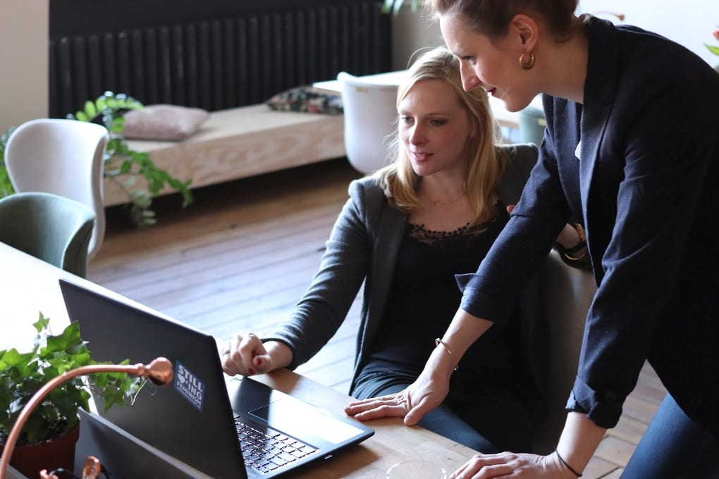Woman standing over another woman's desk and helping with laptop