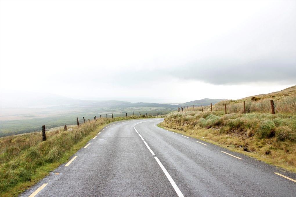 Gray asphalt road near grass under gray sky in daytime.