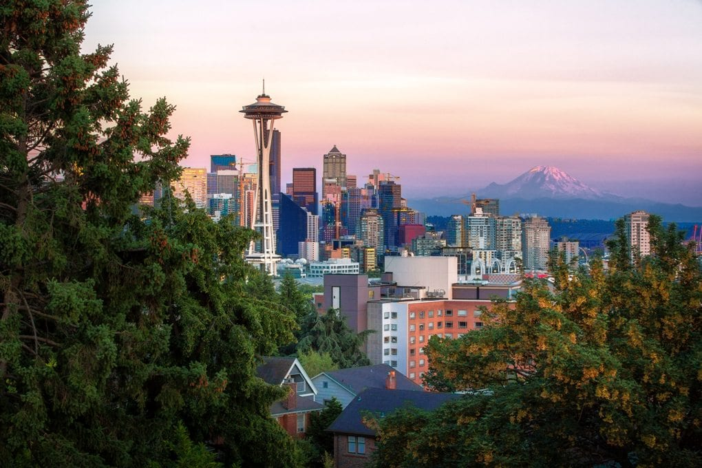Framed by pine trees in the foreground, the Space Needle stands tall above the rest of the Seattle skyline, which sits under a white, orange, and pink sky with Mount Rainier visible in the background.
