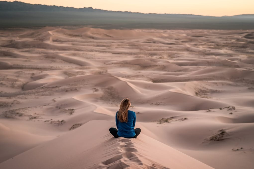 Woman sitting on the sand dunes.