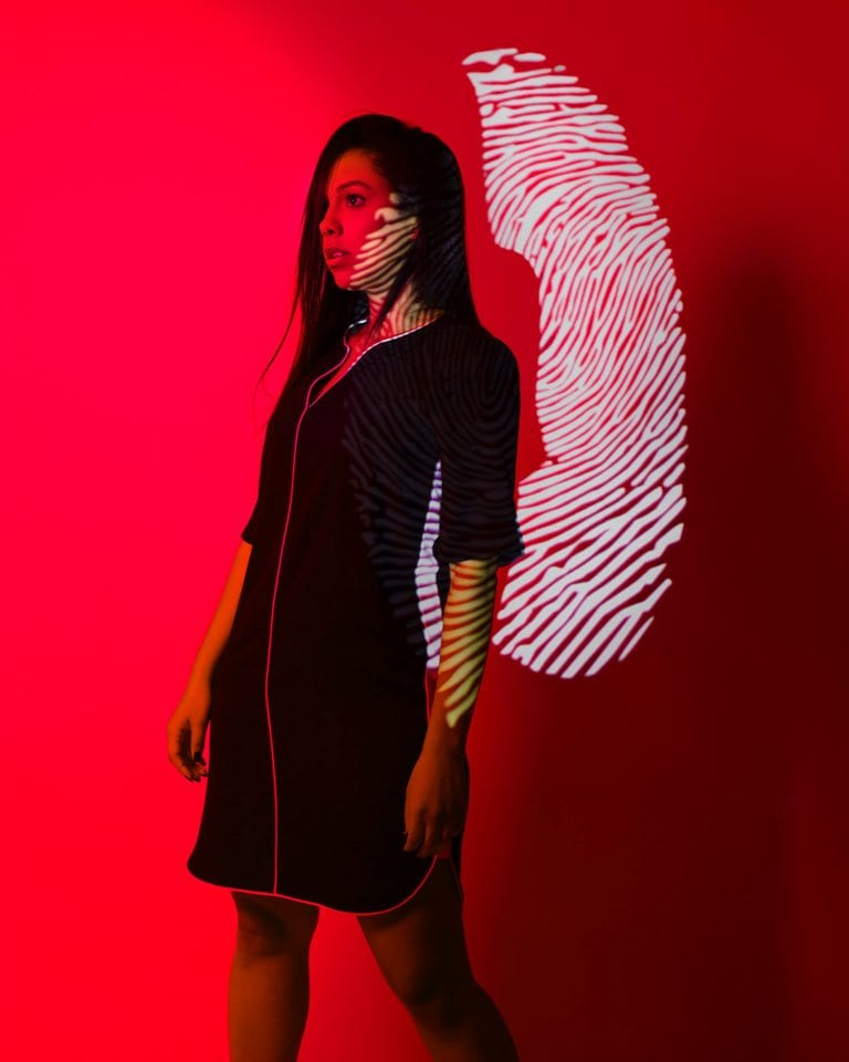a woman stands in front of a fingerprint projected on a red background