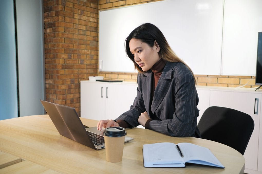 a woman in a black striped blazer works on her silver laptop