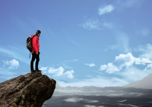 Man standing on top of cliff's edge