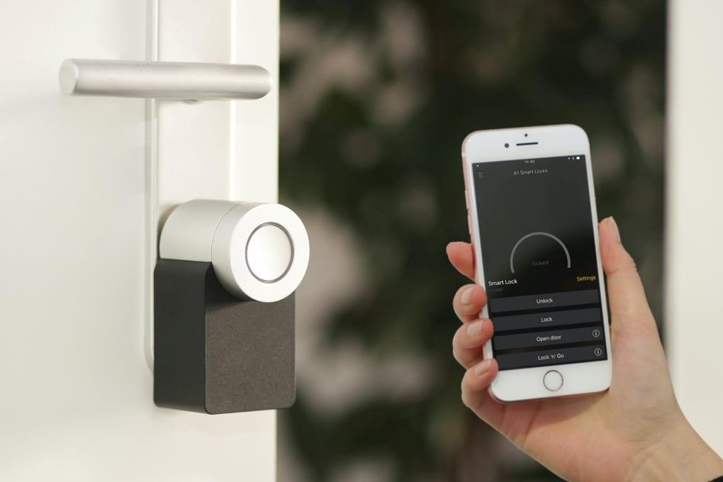 Person holding smartphone next to smart lock on front door