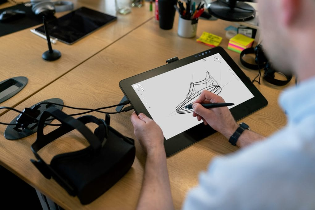 Over-the-shoulder view of a man at his desk sketching out a black drawing on a white tablet background, with a VR headset resting on the desk to his left and a cup of pens, post-it notes in a variety of colors, and headphones to his right.