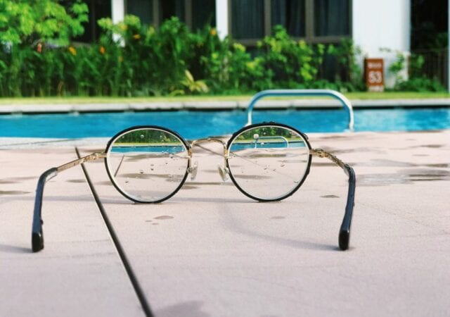 Round-framed glasses sitting on concrete next to swimming pool