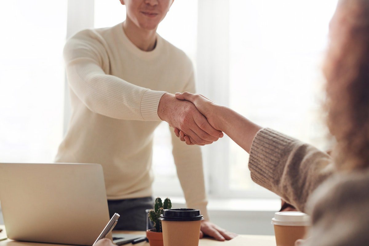 a man shaking a woman's hand at a business meeting. Business Development Manager Interview Questions and Answers
