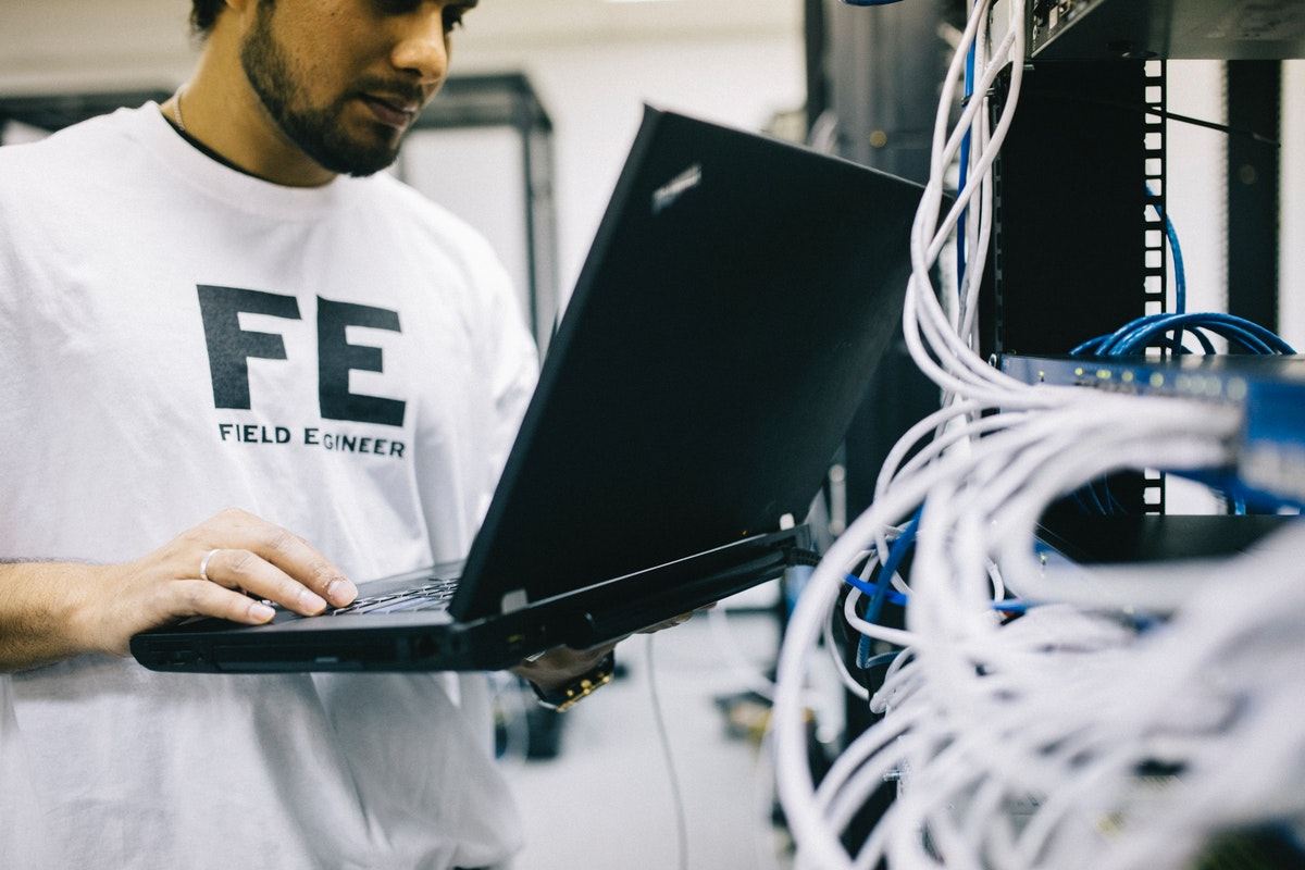 a man examining hardware and working on a laptop Computer Technician Interview Questions and Answers