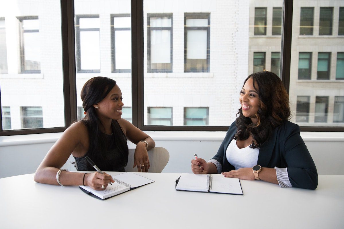 two women exchanging ideas and smiling. Consultant Interview Questions and Answers
