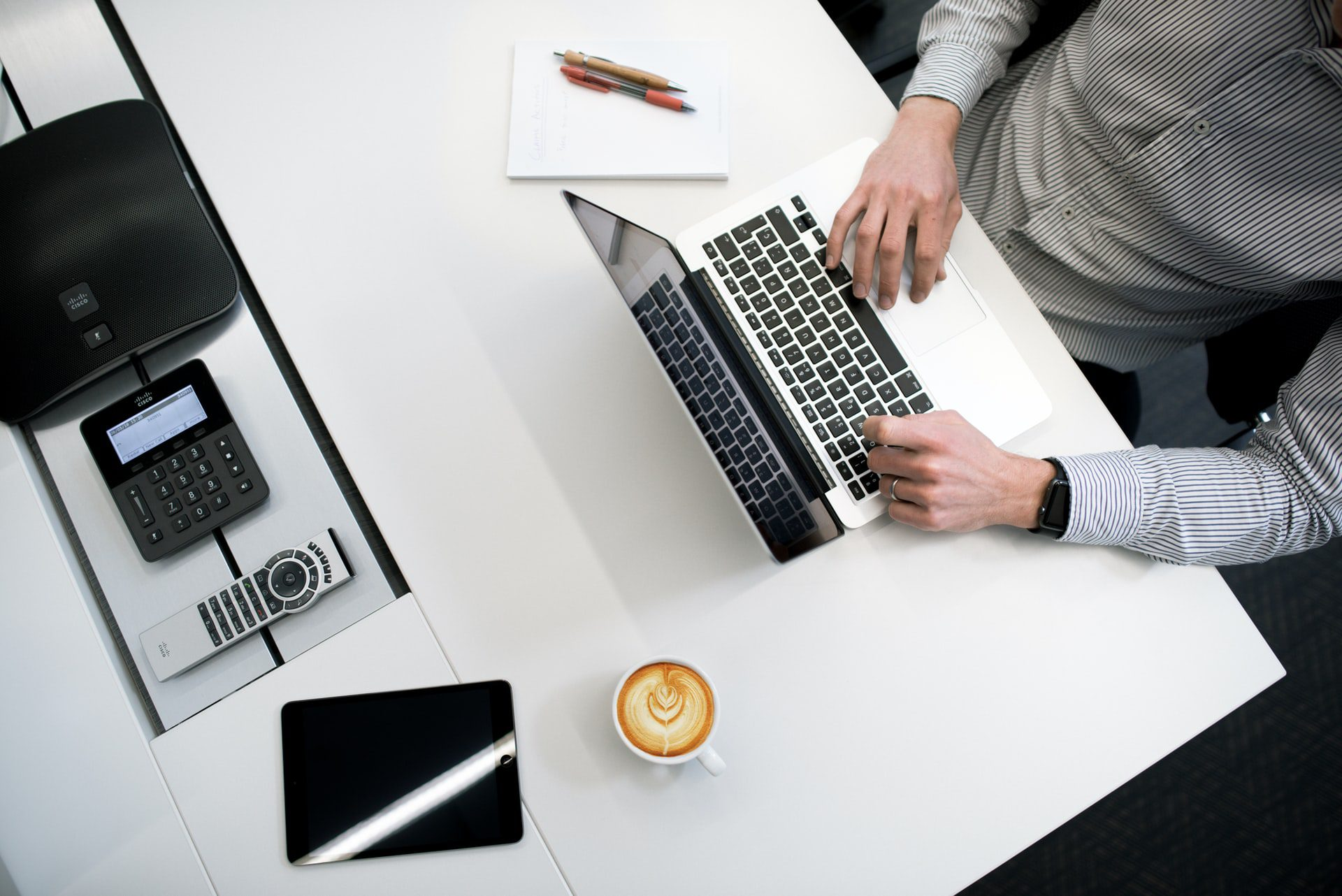 Man using laptop on top of a white wooden table. Copywriter Interview Questions and Answers