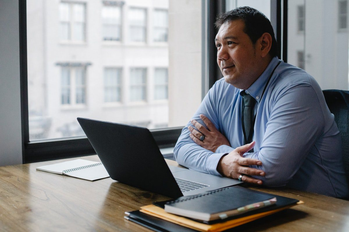 Man wearing a blue shirt and tie sitting in front of a laptop in an office. Director of Finance Interview Questions and Answers