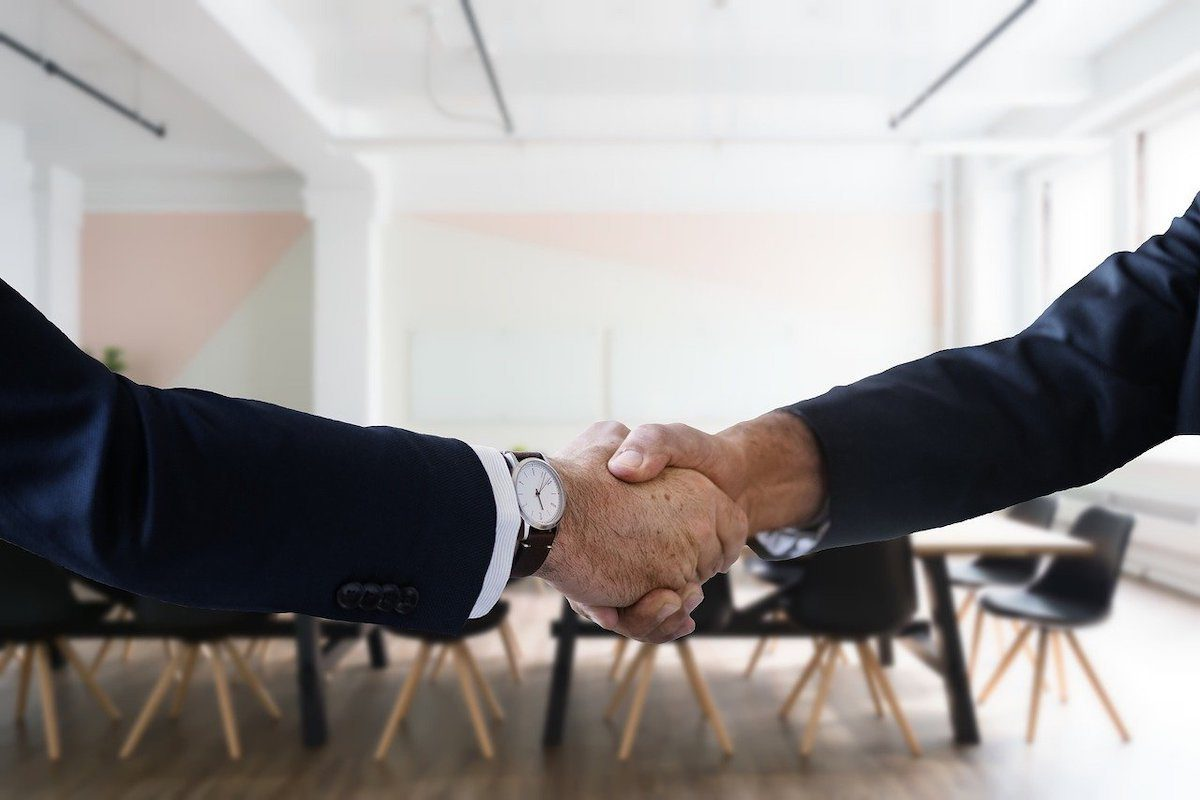 A picture of two people in formal clothing shaking hands in an office. Director of Operations Interview Questions and Answers