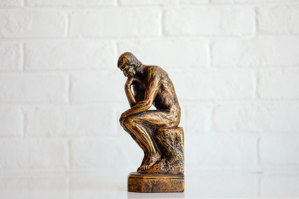 A statue of a thinking man that symbolizes philosophy stands in front of a white wall. best jobs for philosophy majors